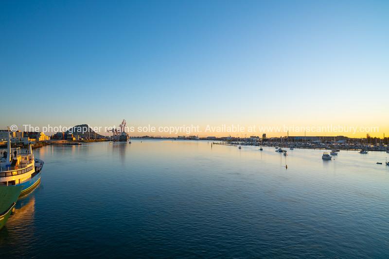 Tauranga harbour at sunrise with port facilities and landmark Mount Maunganui on golden horizon