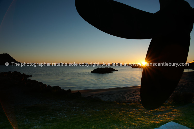 """Sunrises over the Tauranga Harbour. Scene from Sulphur Point framed by the old tug boat Taioma's propeller. Tauranga is New Zealands 5th largest city and offers a wonderfull variety of scenic and cultural experiences. Tauranga stock images Tauranga scenics. See;  <a href=""""http://www.blurb.com/b/3811392-tauranga"""">http://www.blurb.com/b/3811392-tauranga</a> mount maunganui landscape photography, Tauranga Photos; Tauranga photos, Photos of Tauranga Also see; <a href=""""http://www.brianscantlebury.com/Events"""">http://www.brianscantlebury.com/Events</a>"""