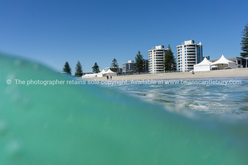 Surf wave forms with apartment buildings and beach