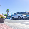 Maunganui Road in main shopping area with passing vehicles and people,