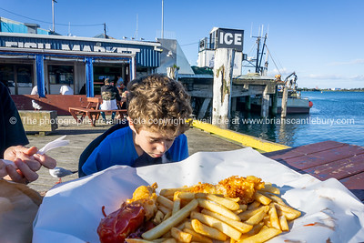 Small boy in blue jersey outside fish market with srpead of fish