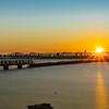 Sun rises over horizon across bay.