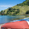 Upturned dinghies and waka-ama being paddled across Pilot Bay