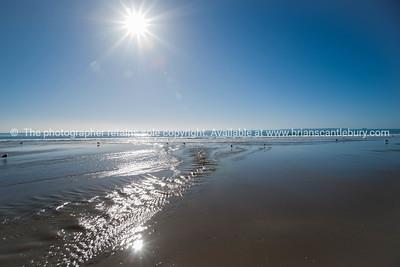 Papamoa Beach. Sun flare over sea and beach.