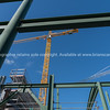 Construction site from low angle with heavy steel formwork and yellow crane.