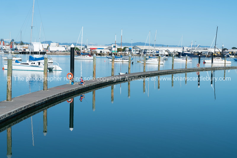 Long curving pier surrounded by blue calm water