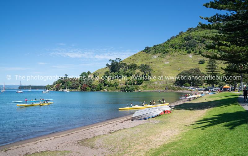 Pilot Bay at base of Mount Maunganui with active people paddling waka-ama on beautiful summers day.