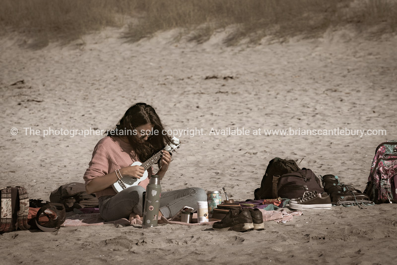 Woman sitting alone on beach playing ukelele surrounded by belongings. Releases; NO, please use for personal and editorial only.