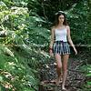 Pretty teenage girl walking barefoot through forest