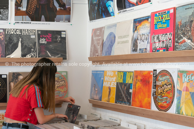 Young woman in red top checking through vintage vinyl records