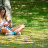 Attractive teenage girl sitting at base of tree
