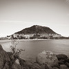 Mount Maunganui, popular travel and holiday destination with landmark mountain beyong long white beach and rocky foreground.