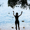Teenage girl stands by lake edge with ducks in water