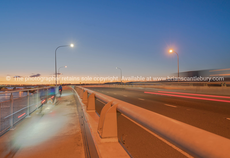 Tauranga Harbour Bridge transport route with road and pedestrian and cycle path with glow of cyclists and vehicle passing lights