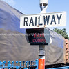 Railway sign and passing cargo train