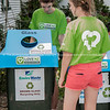 Girls checking  bin dressed in green teeshirts with Love NZ recycling emblem