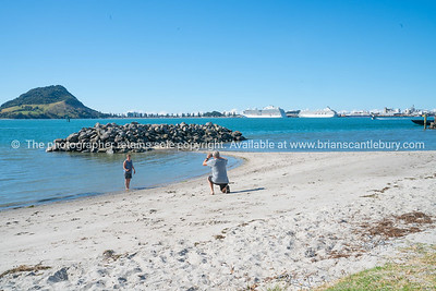 Couple enjoying beach taking photograph with view across Tauranga harbor from Sulphur Point to landmark Mount Maunganui and berthed cruise ships.