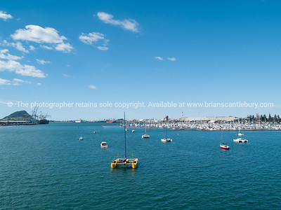 Tauranga Harbour. With port facilities on both sides and iconic Mount Maunganui on horizon, from Tauranga Harbour Bridge.