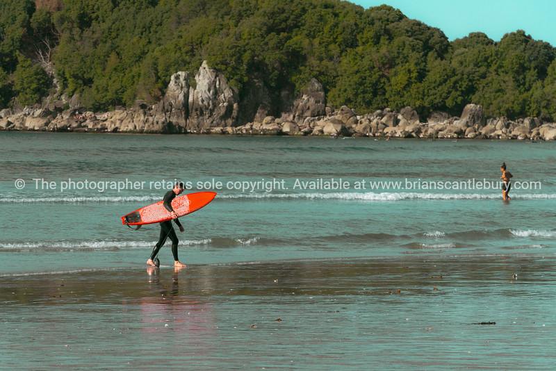 Vintage effect surfer leaving water carrying orange surfboard.