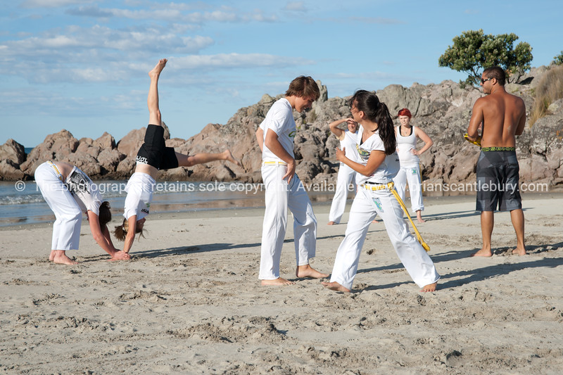 """Capoeira being practised on Mount Maunganui beach, Tauranga, New Zealand.<br /> Capoeira is a game, a sport, an art and a life philosophy, founded in Brasil in 1984. - 8<br /> Model Release; no. See;  <a href=""""http://www.blurb.com/b/3811392-tauranga"""">http://www.blurb.com/b/3811392-tauranga</a> mount maunganui landscape photography, Tauranga Photos; Tauranga photos, Photos of Tauranga Also see; <a href=""""http://www.brianscantlebury.com/Events"""">http://www.brianscantlebury.com/Events</a>"""