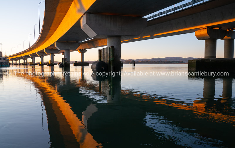 Morning sun strikes side Tauranga Harbour Bridge in golden hue reflected leading lines into calm water below
