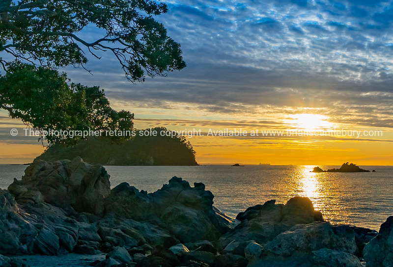 Sunrises over distant horizon along beach from rocky foreground