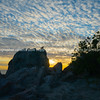 Silhouette rocky outcrop with two oystercatchers and puffy cloudy sky at sunrise
