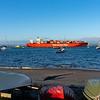Large orange cargo ship, Hamburg Sud, leaves Port of Tauranga loaded with Maersk containers