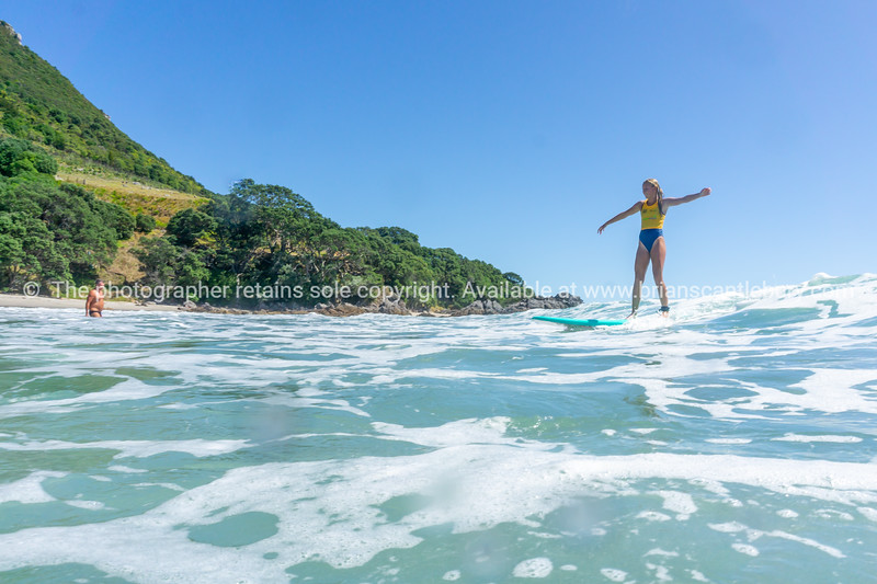 Young woman surfer rides the wave arms out for balance. Model released; NO, please use for personal or editorial only.