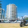 Cruiser motorbike parked on berm at Mount Main Beach with Oceanscide twin Towers background.