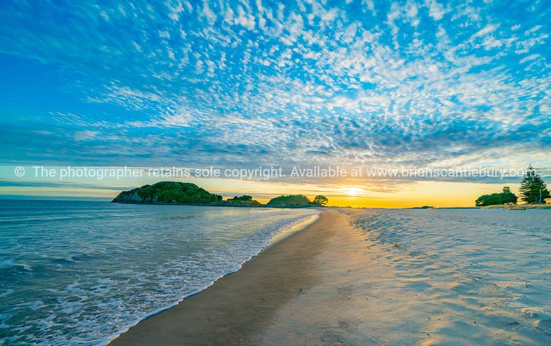 Mount Maunganui Main Beach with Moturiki Island as sun rises over horizon.