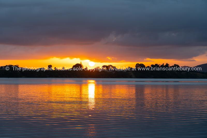 Intense golden sunrise between layer of dark cloudy sky and sea