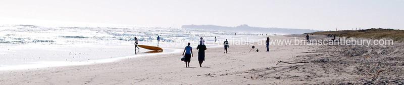 Beach walkers and a lone kayaker drags his kayak to the waters edge.