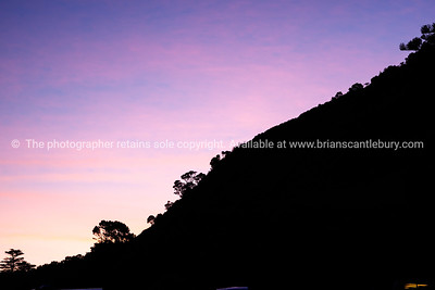 Mount Maunganui slope silhouetted against evening sunset. Mount Maunganui beach scenes.
