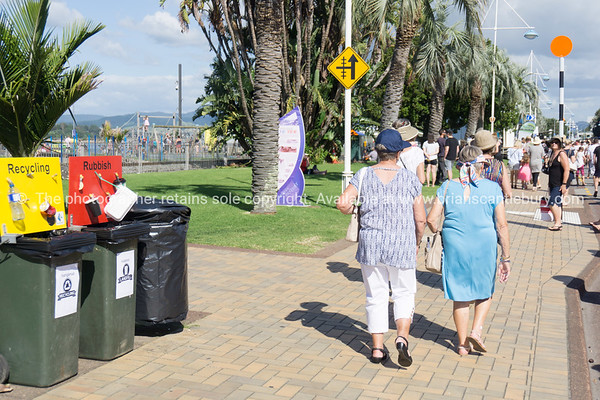 People walking on footpath past recycling bins.