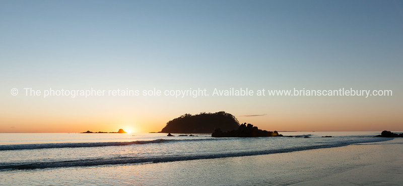 Sunrises over horizon from foreshore next to Leisure Island or  Moturiki.