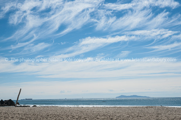 Cirrus cloud formation above Mount maunganui ocean beach. Mayor Island on horizon.
