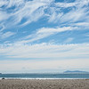 Cirrus cloud formation above Mount maunganui ocean beach. Mayor Island on horizon.