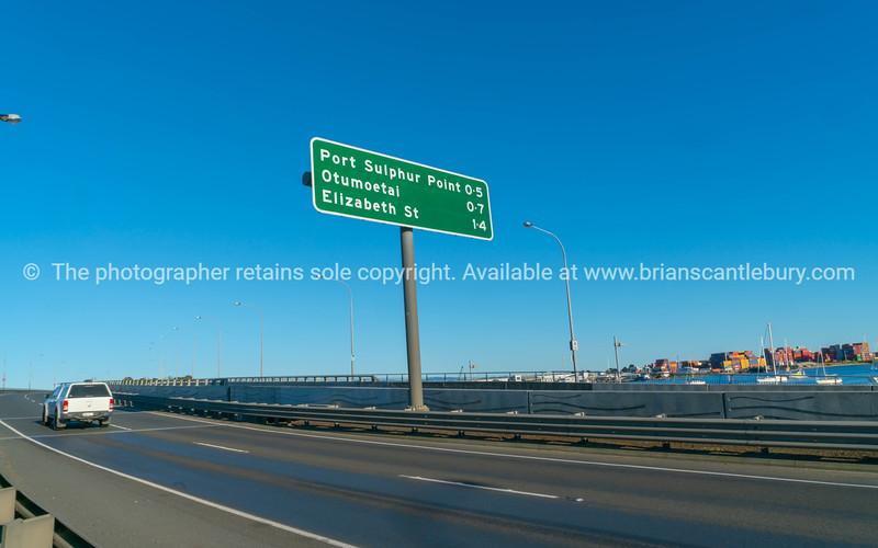 Road direction sign on Tauranga Harbour crossing bridge against blue sky