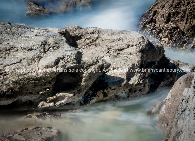 Waves smoothed by long exposure washing in around rocky foreshore.