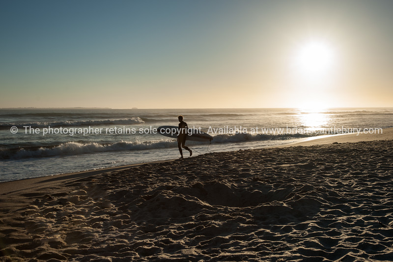 Lone surfer heads to water as sun rises.