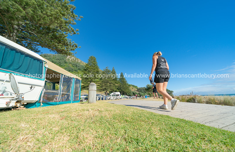 Boardwalk leading to base of Mount Maunganui along in front campers and caravans.