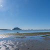 Dinghy lies on sand at low tide with Mount Maunganui on horizon.