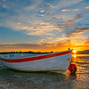 Backlighting of dinghy on beach by sunrise across harbour and behind distant hills.