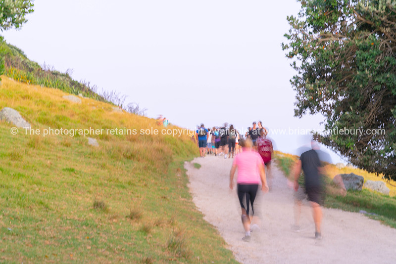 Blurred images of large group people walking up sloping track of Mount Maunganui at sunrise.