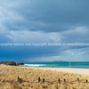 Bollards mark out access through dunes to Main Beach  with it's white sand turquoise water under deep blue rainclouds on horizon.