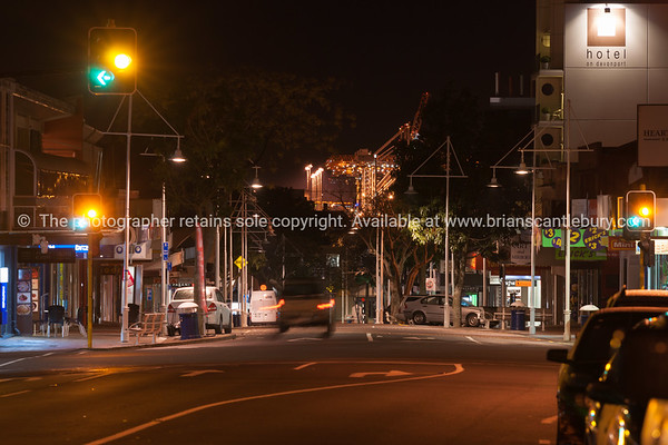 Tauranga's Devonport Road night scene with port cranes illuminated seemingly at end of road.
