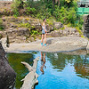 Rock pool with log in water and attractive girl standing on other side.