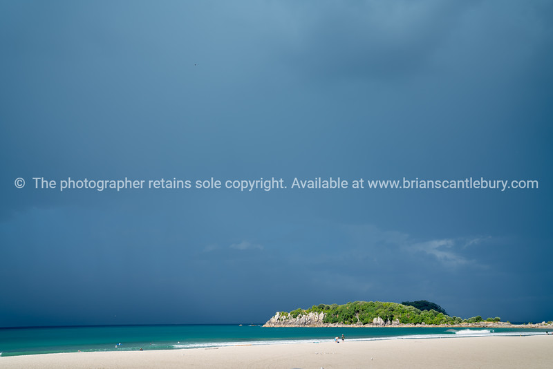 White sandy beach and Leisure Island caught in sun against background dark blue raincloud sky.