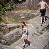 Young male running away and female running toward on rocks having fun in summer sun.